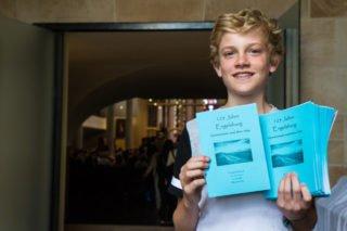 Herzlich willkommen: Henning Claus aus der sechsten Klasse teilt am Eingang der Martinskirche die Liederhefte mit aus. Foto: SMMP/Bock